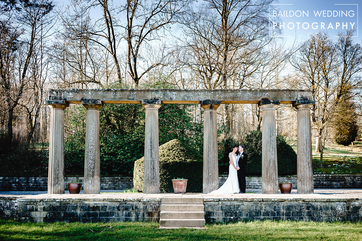 bride and groom stand amongst the ruins of the original house at the coniston hotel in skipton for their Yorkshire wedding