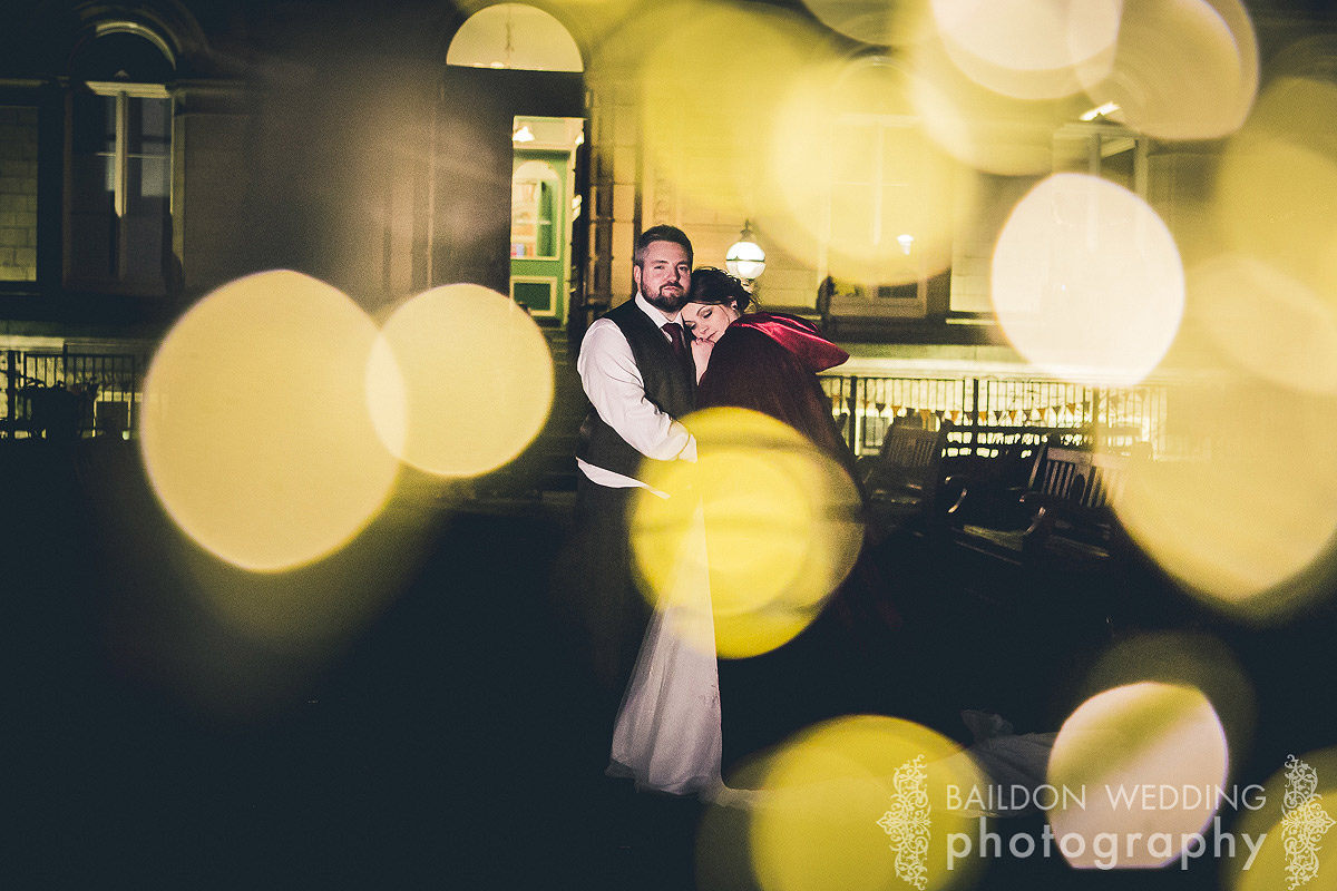 bride and groom, bokeh lights night shot outside Victoria Hall Saltaire
