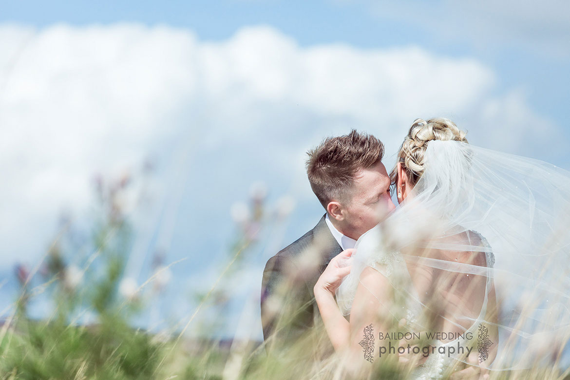 Groom whispers to his bride as her veil blows in the breeze on the moorland during their Yorkshire wedding photography session on their wedding day. Bokeh foliage in the foreground and blue skies overhead.