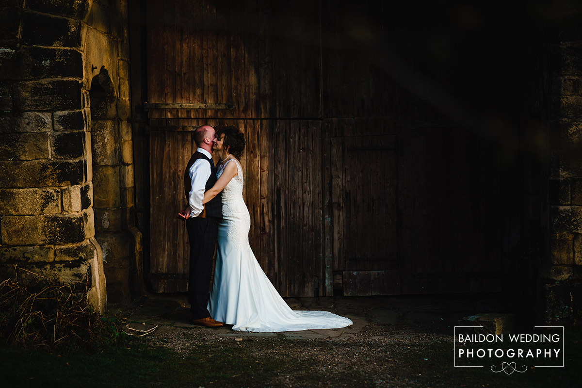 barn door couple snuggle at East Riddlesden Hall
