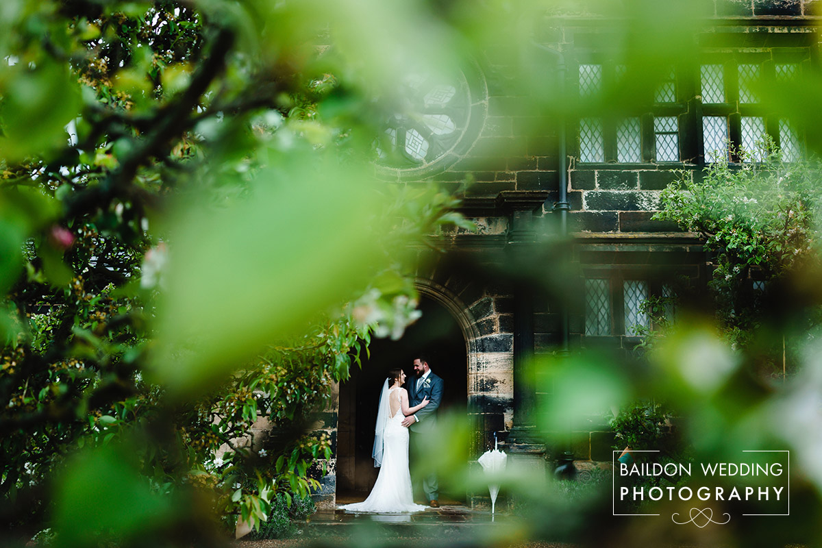 Fiona and Stuart on their wedding day in front of the grand hall at East Riddlesden Hall, photographed through the leaves