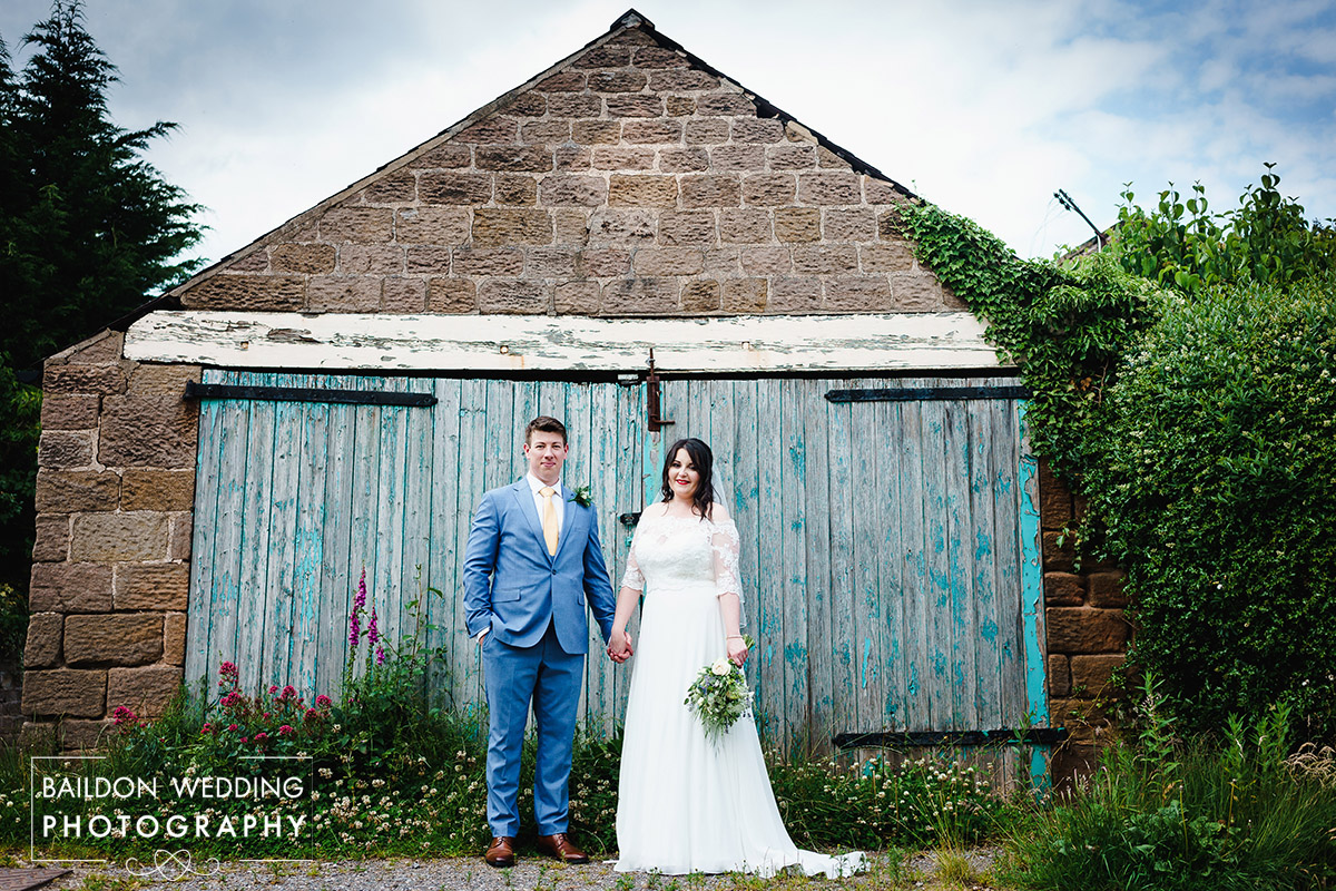 Bride and groom stood in front of old garage in Sicklinghall Village